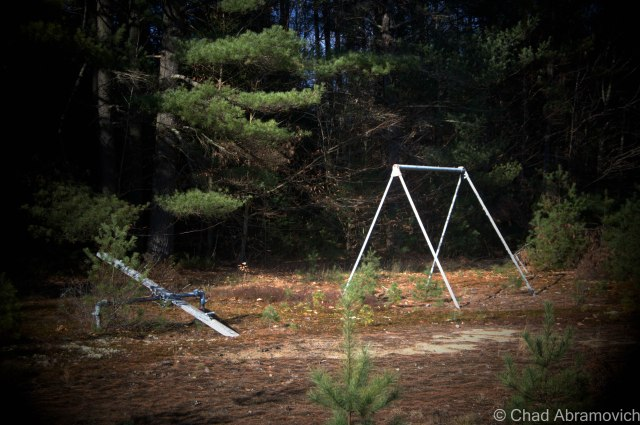 An abandoned playground weighed down by the desolation of the forest.