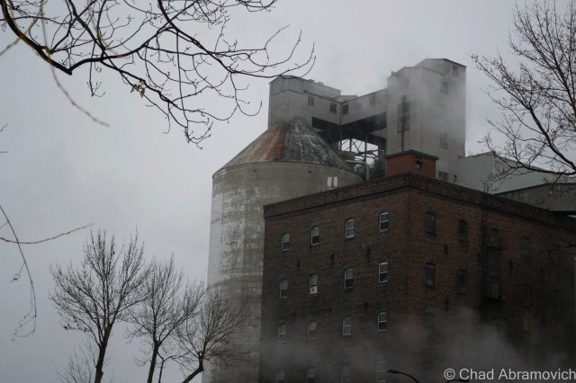 The mists that weighted down the Saint Lawrence tides curled around a grain silo on the side of Rue Notre-Dame