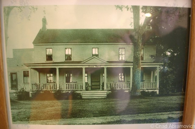 """An original picture of the Eddy Brothers Farmhouse. (I think circa 1920-1930). Notice the name """"Lake View"""" above the porch? The Eddy Brothers Farmhouse used to be surrounded by a beautiful pond, the house sitting on a peninsula in the middle. Older photos of the farm show the barns sitting across the bays of the pond with the house in the foreground. However, In the early 1900s, the beaver dam burst, and within hours, the pond had drained. Today, the ravine where the former pond was can still be traced, now filled in with younger growth trees and countless berry bushes."""