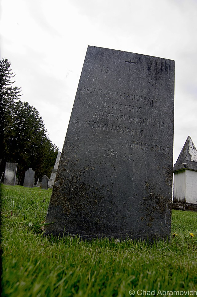 In Middlebury's West Cemetery, a innocuous headstone has some rather strange markings. For example, the date of death is 1883, B.C! An error on the stonecutter's part, right? Nope. This is the grave of Amun-Her-Khepesh-Ef, Vermont's only royal figure, the 2 year old son on an ancient Egyptian king. But how did he wind up in Addison County? We have Henry Sheldon to thank, who over a century ago bought the mummy from a dealer in New York. A wealthy man and local oddities collector, he wanted the mummy to be the focal point of an ostentatious cabinet of curiosities he was building. But the mummy was in worse condition than the dealer said it was in, so he wound up disappointedly stashing it in his attic. It was rediscovered in 1945 by a curator of the related Sheldon museum. George Mead, head of the museum's board of directors, decided the best thing to do was to give the mummy a Christian burial by cremation and then buried the ashes in his family plot in West Cemetery, kinda like an adoption.